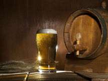 Beer barrel with beer mug on wooden background. Beer barrel with beer mug on a wooden dark background royalty free stock photo