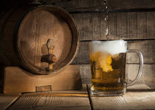 Beer barrel with beer mug on wooden background Royalty Free Stock Image