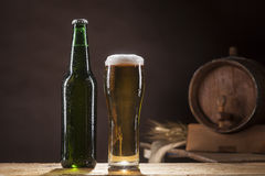 Beer barrel with bottle and mug on brown background. Beer barrel with beer mug and buttle on a brown dark background royalty free stock photo