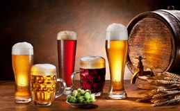 Beer barrel and draft beer by the glass. Dark background royalty free stock image