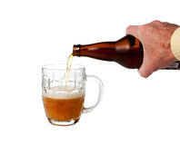 Beer being poured from bottle. Golden ale being poured from brown bottle into half full english pint mug royalty free stock photo