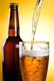 Beer Being Poured in Glass and Bottle. On yellow background Stock Images
