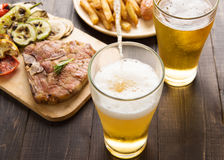 Beer being poured into glass with gourmet steak and french fries. On wooden background Stock Photos