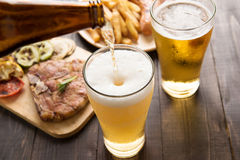 Beer being poured into glass with gourmet steak and french fries. On wooden background Stock Image