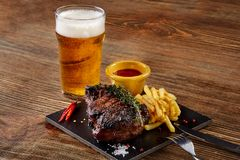 Beer being poured into glass with gourmet steak and french fries on wooden background. Copy space. Still life. Served at restaurant, cafe, bar, pub Royalty Free Stock Photo