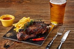 Beer being poured into glass with gourmet steak and french fries on wooden background. Copy space. Still life. Served at restaurant, cafe, bar, pub Stock Photography