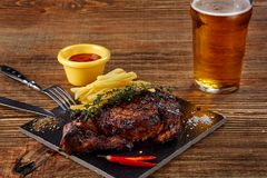 Beer being poured into glass with gourmet steak and french fries on wooden background. Copy space. Still life. Served at restaurant, cafe, bar, pub Stock Image