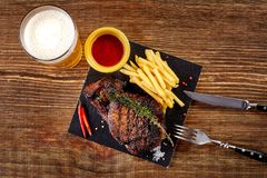 Beer being poured into glass with gourmet steak and french fries on wooden background. Top view. Beer being poured into glass with gourmet steak and french fries Royalty Free Stock Photos