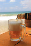 Beer being poured into a glass on an idyllic beach. Bottle of beer being pored on an idyllic beach with the ocean and blue sky in the background symbolizing Royalty Free Stock Photography
