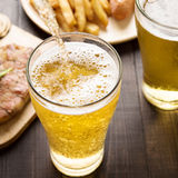 Beer being poured into glass with steak and french fries on wood. En background Royalty Free Stock Photography