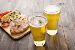 Beer being poured into glass with steak on wooden background Stock Photo