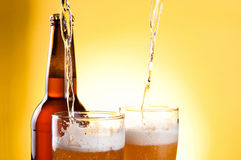 Beer Being Poured in Two glasses and Bottle. On yellow background Royalty Free Stock Photos