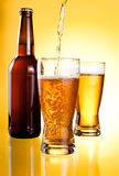Beer Being Poured in Two glasses and Bottle. On yellow background Stock Images
