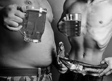 Beer belly. Two men with big beer bellies stock photo