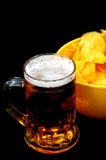 Beer on black. Beer and potato chips on black royalty free stock photo