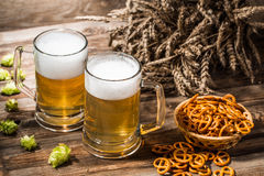 Beer in blackjack, hops, wheat spikes on table Stock Photo