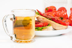 Beer,BLT and Field Tomatoes. A front angled view of a glass of beer with an open-face BLT sandwich and a tilted basket of field tomatoes in the background. Sharp Royalty Free Stock Image