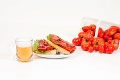 Beer,BLT and Field Tomatoes Angled Front View. A front angled view of a glass of beer with an open-face BLT sandwich and a tilted basket of field tomatoes in the Royalty Free Stock Image