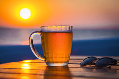 Beer with bokeh in the sea. Cold Draught Beer with bokeh of the sunset in the sea background Stock Images