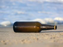 Beer bottle. Brown beer bottle laying on the sand. Close-up Stock Photo
