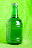 Beer bottle against green Royalty Free Stock Images