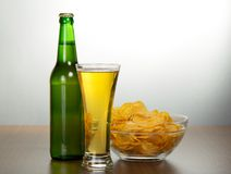 Beer bottle, bowl with chips and a damp glass Royalty Free Stock Photography