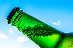 Beer in bottle with bubbles closeup on blue sky background Royalty Free Stock Image