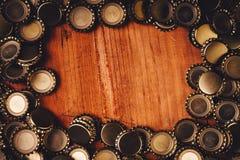 Beer bottle caps frame over wooden background Stock Images