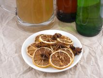 Beer bottle with cinnamon and lemon on white plate Stock Photos