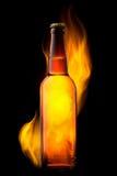 Beer bottle in fire on black Stock Photo