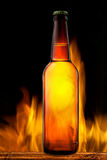 Beer bottle in fire on black Stock Photos