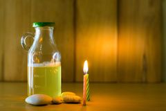 Beer bottle and fire of candles put on wood with wooden background using wallpaper for party at night. Royalty Free Stock Image