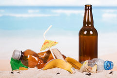 Beer bottle, food and household waste in sand on seashore. Stock Images