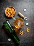 Beer in a bottle and a glass of snacks in the bowl. On rustic background royalty free stock image