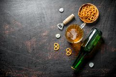 Beer in a bottle and a glass of snacks in the bowl. On rustic background stock images