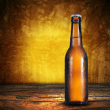 Beer bottle on grunge background Royalty Free Stock Photo