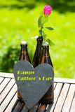 Beer bottle with heart and roses for Father`s Day. Romantic stock image