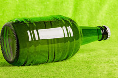 Beer bottle laying over green Royalty Free Stock Photography
