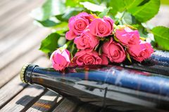 Beer bottle lying with roses for Father`s Day. Garden royalty free stock photo