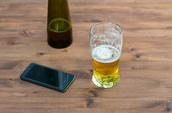 Beer, bottle, and mobile phone Stock Photography