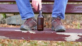 Beer bottle near man's dirty boots stock footage
