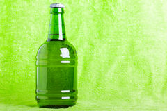 Beer bottle over green Royalty Free Stock Photos
