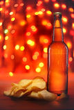 Beer bottle and potato chips Stock Images