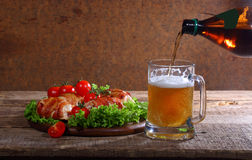 Beer from a bottle pour in a transparent mug. Beer and chicken beaters royalty free stock photos