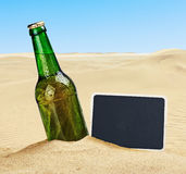 Beer bottle in the sand in the desert and the blackboard. For writing Stock Image