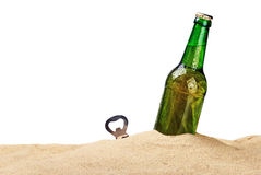 Beer bottle in the sand isolated Stock Image