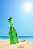 Beer bottle on a sandy beach, with clear sky and sun Royalty Free Stock Image