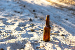 Beer bottle on a sandy road royalty free stock images
