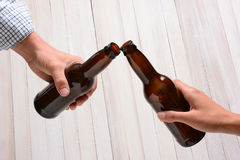Beer Bottle Toast. A man and a woman toasting with beer bottles. They are clinking the bottle tops over a rustic wood background Royalty Free Stock Photography