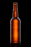 Beer bottle with water drops on black Royalty Free Stock Photo